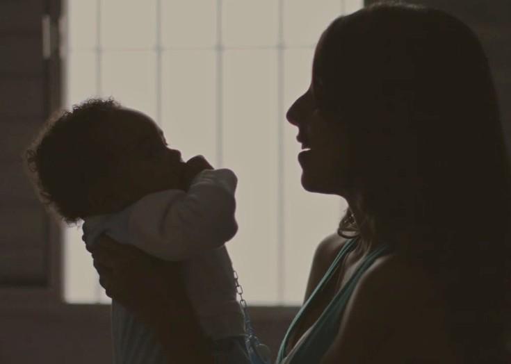 Sombra de uma mulher, com cabelos longos, segurando um bebê no colo, que está com o dedo na boca.